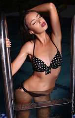 beautiful girl in bikini posing in night swimming pool
