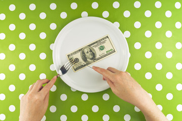 Woman eating hundred dollar bill for dinner