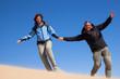 Coppia allegra corre sulla sabbia del deserto