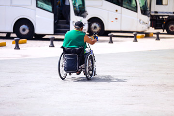 Man riding in a wheelchair, self-sufficient