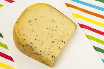 Piece of Dutch cheese with herbs on a cutting board