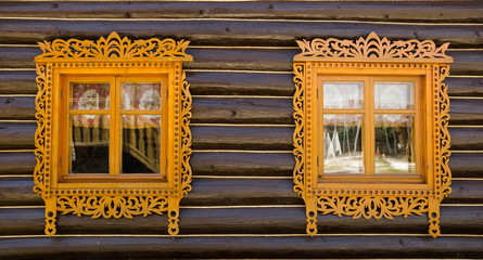 Windows with carved wooden architraves in  log house