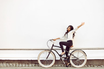 Beautiful happy woman sitting on bicycle and giving salute gestu