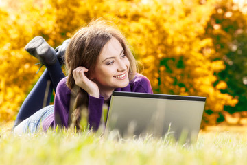 Woman with laptop in autumn scenery