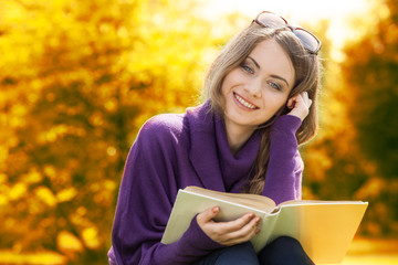 Woman reading book in autumn scenery