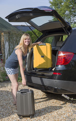 Woman putting suitcases into car trunk