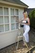 Painter decorator painting windows standing on steps