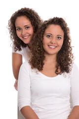Reale Zwillinge: Portrait von zwei Schwestern freigestellt