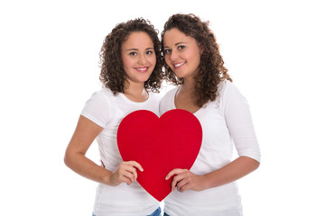 Rotes Herz Konzept: zwei lachende Mädchen; reale Zwillinge