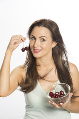 Attractive woman eating cherries from a packet