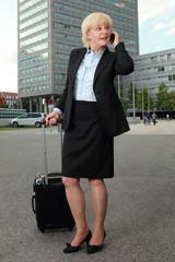 Geschaeftsfrau mit Rollkoffer beim Telefonieren