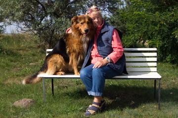 Seniorin mit Hund sitzt auf einer Bank