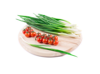Onions and cherry tomatoes on a wooden board.