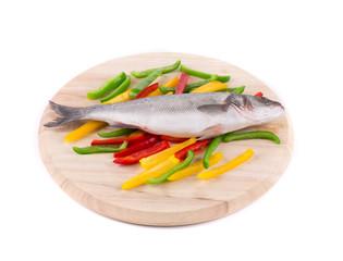Fresh seabass fish on wooden platter.