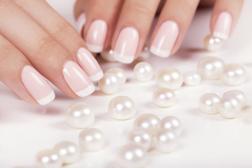 Beautiful woman's nails with french manicure and pearls.
