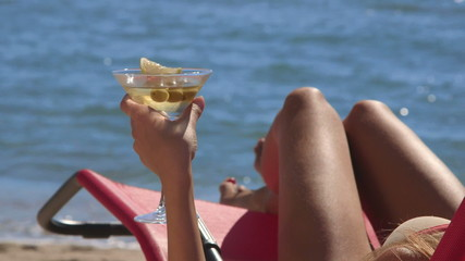 Female hand holding martini cocktail with olives on  beach