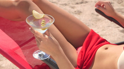 Young woman holding martini cocktail with olives on beach