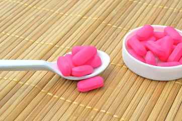 Pink medicine tablet on the spoon
