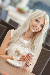 Beautiful model woman with the cup of hot beverage in restaurant