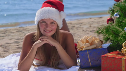 Smiling pretty woman with gifts Christmas tree on beach