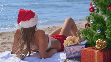 Pretty Santa with gift boxes under Christmas tree on beach