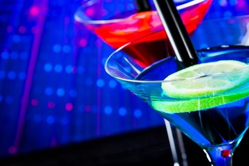 top of view of cocktail with blue light disco background