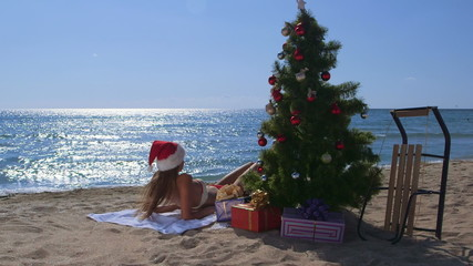Girl in red Santa hat enjoying Christmas vacation  on  beach