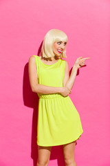 Blonde girl in lime green dress pointing