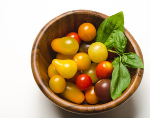 Cherry tomatoes and basil leaves in wood bowl