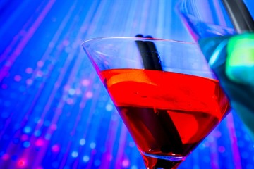 red cocktail with blue light disco background