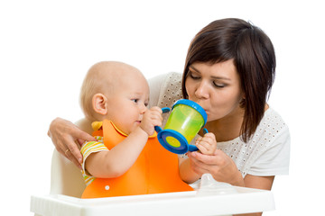 kid giving to mom water from his feeding cup