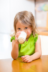kid girl drinking yogurt or milk in kitchen