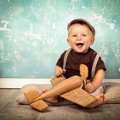 kleines Baby mit Holzflugzeug