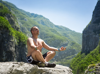 Man  sitting on a rock and meditating