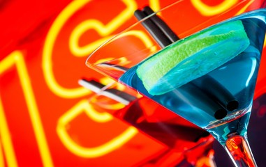 detail of cocktail with neon disco word background