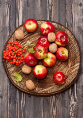 Red apples on textured wooden background. Autumn composition.