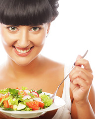 Young happy woman eating salad.
