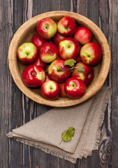 Red apples in rustic wooden bowl