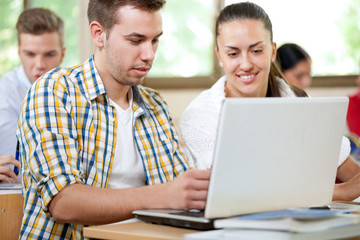 students with laptop in classroom