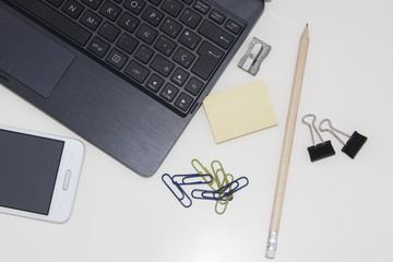 Workspace with laptop, mobile, clips, pencil, post it over white