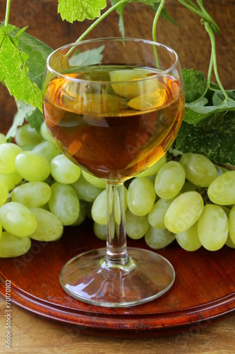 glass of white wine with grapes on a wooden background © dream79