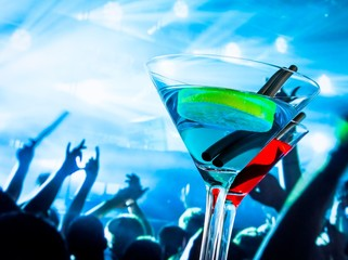 blue and red cocktail drink on a disco table with space for text