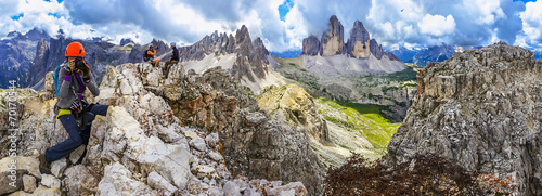 Young woman taking a photo on one of the peaks of the Dolomites © A.Jedynak
