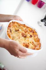 Eine Frau hält eine Lasagne in der Küche