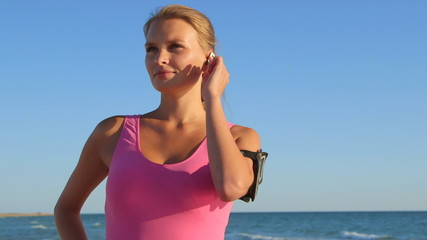 Fitness athletic girl using sport  headset while exercising
