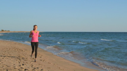 Fitness girl jogging on beach listening music during workout