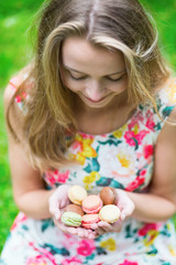 Young girl holding French macaroons in hands
