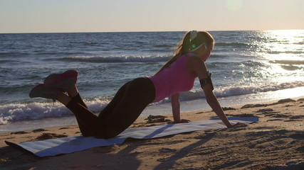 Fitness woman doing push-ups during sports training on beach