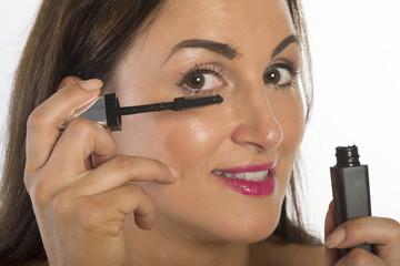 Woman applying black mascara to her eyelashes