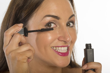 Woman applying black mascara to her eyelashes